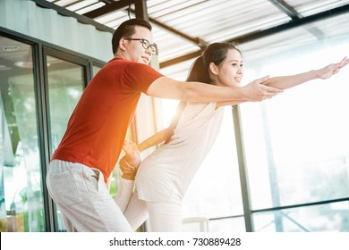 Asian couples is exercise. The man is teach yoga to women.