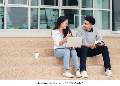 Asian couples students or colleagues sitting at the stairs and smiling as they use laptop computer and girl show thumb up at campus.