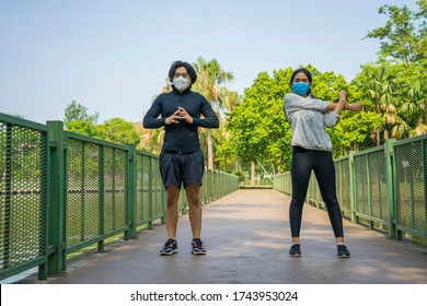 Asian couples wear masks that protect against covid 19 so happy and warming up together for health in the park.Social distancing ,work out and New normal concept.
