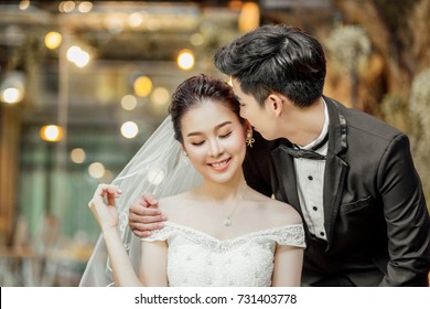Asian couples are whispering and tell some sweet wording with smiling faces.