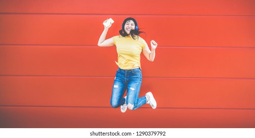 Asian crazy girl jumping and listening music outdoor - Happy chinese woman celebrating and dancing outside - Fun, millennial generation and technology trends concept - Focus on body