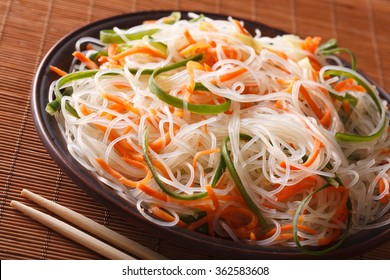 Asian crystal noodles with cucumber and carrot on a plate close-up. Horizontal