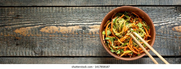 Asian cucumber and carrot salad with sesame, garlic, soy sauce and cilantro. top view. place for text. copy space.