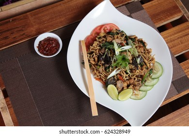 asian cuisine fried noodle mixed with meat and vegetables with chili sauce