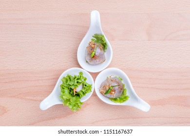 Asian cuisine healthy appetizers, fresh vegetable spring roll and sago ball with pork filling served on small canape spoon on wooden board background.