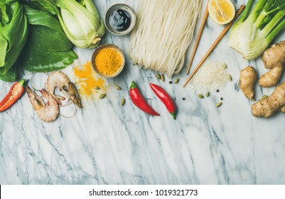 Asian cuisine ingredients over marble background, top view, copy space. Flat-lay of vegetables, spices, shrimp, sauces for cooking vietnamese, thai or chinese food. Clean eating, vegetarian concept