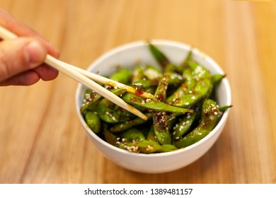 Asian Cuisine - Roasted Green Beans With Sweet And Sour Sauce, Pepper And Sesame In White Bowl On Wooden Table. Close-Up.