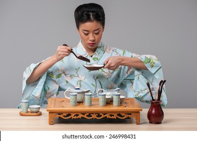 Asian culture. Young beautiful Japanese woman in traditional kimono getting ready to perform tea ceremony with tea tools on the table against grey background