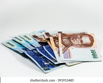 Asian currency on white background. 1000 Thai banknotes and 1000 New Taiwan Dollar banknotes.