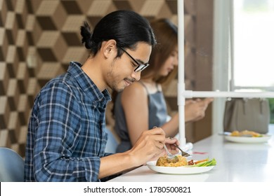 Asian customer eating out at new normal social distance restaurant with table shield partition reduce infection of coronavirus covid-19 pandemic. Restaurant new normal lifestyle.