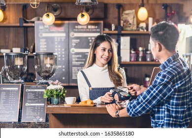 Asian customer man paying with credit card via contactless nfs technology to Asian Barista of Small business owner at the table in coffee shop, Small business owner and startup in coffee shop concept