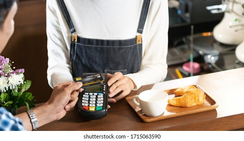 Asian customer using contactless credit card nfs technology pay to barista at cafe bar. Contactless payment preventing from coronavirus covid-19 Spreading and infection, Panoramic web banner crop.