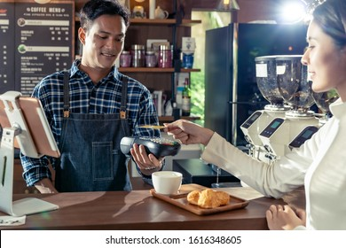 Asian customer using her credit card with contactless nfs technology to pay a barista for her coffee purchase at a cafe bar.