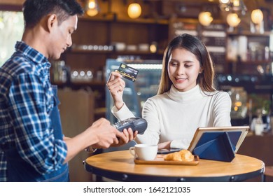 Asian customer woman paying with credit card via contactless nfs technology to Asian Small Coffee shop owner at the female table in cafe, Small business owner and startup in coffee shop concept