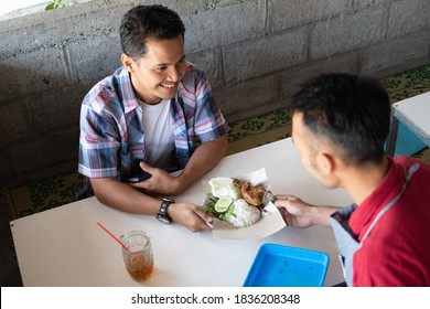 Asian customers smile holding their cell phones as the restaurant waiter presents his orders