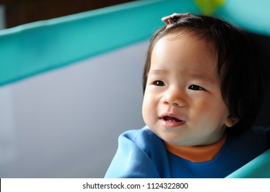 Asian cute baby girl looking over side of travel cot or playpen.