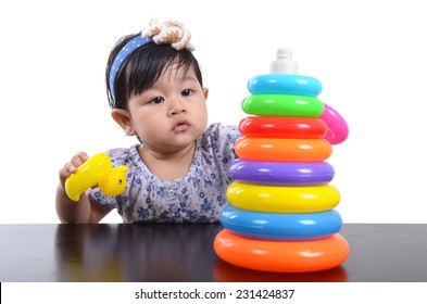 Asian cute baby girl playing with colorful pyramid toy isolated on white background