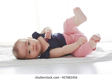 Asian cute baby, lying on his back and holding legs