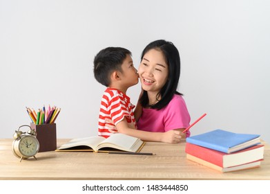 Asian cute boy doing his school homework with his mother, at home, he kiss his mother..Education concept