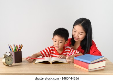 Asian cute boy doing his school homework with his mother, at home, he is writing on a book.Education concept