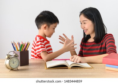 Asian cute boy doing his school homework with his mother, at home, Education concept