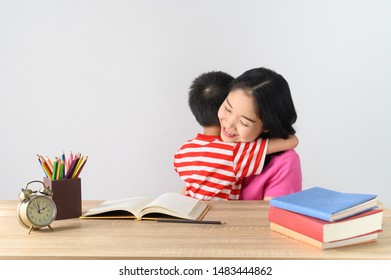 Asian cute boy doing his school homework with his mother, at home, he hug his mother.Education concept