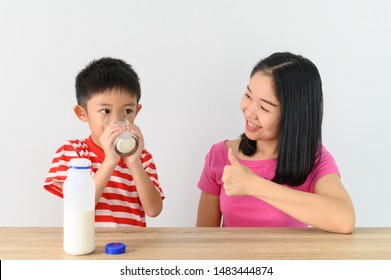 Asian cute boy drinking milk with his mother, white wall at home, .Food and drink concept with copy space
