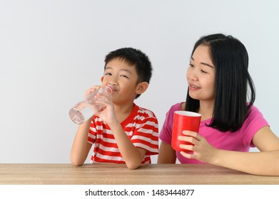 Asian cute boy drinking water with his mother, white wall at home, .Food and drink concept with copy space