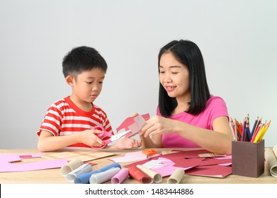 Asian cute boy making handicraft  with his mother, white wall at home, Education hobby family concept with copy space