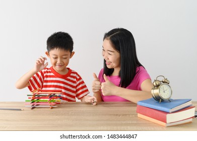 Asian cute boy playing game with his mother, white wall at home, .Education concept with copy space