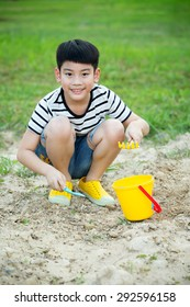 Asian cute boy playing with toys in garden