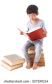 Asian cute boy reading book while sitting on stack of books. white background.