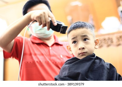 Asian cute boy trying to sit still for a barber in THAILAND