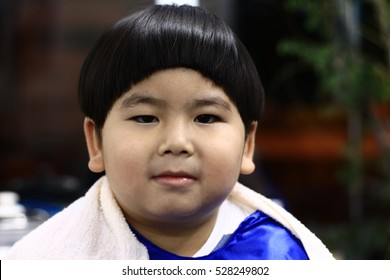 Asian cute boy trying to sit still for a barber THAILAND, Cute child scared and doesn't like to cut my hair