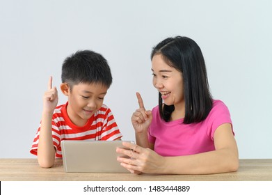Asian Cute boy watching tablet with his mother  at white wall in room. Learning by smart phone take care by family concept