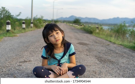Asian cute child girl Sitting on the reservoir road