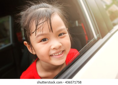 Asian cute child smiling and wear red T-shirt in car, happy to travel with family, warm color tone and sunlight, soft focus, happiness concept
