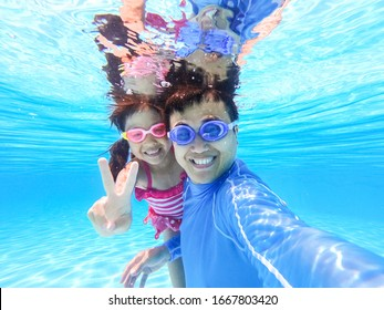 asian cute daughter and father play and selfie happily in the swimming pool