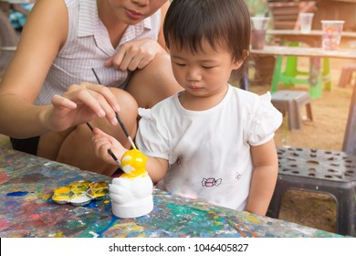 Asian cute girl baby and mother is painting colorful in the park.
