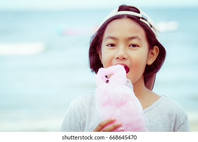 Asian cute girl eating candy floss on the beach in summer with vintage color tone