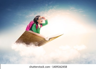 Asian cute girl with glasses and backpack sitting on the book with blue sky background. Back to School concept