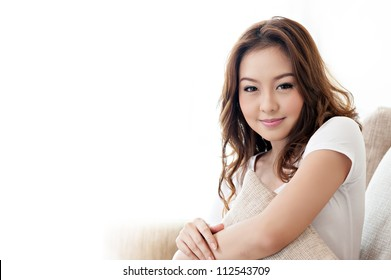 Asian cute girl holding pillow in living room