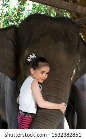 Asian cute girl hug elephant happy face at Chiang Mai, Northern Thailand.