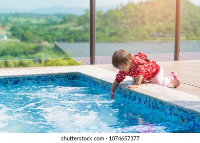 Asian cute girl kid want to play water in the pool, sunny light background, vacation holidays family concept in resort mountain, luxury summer hotel.