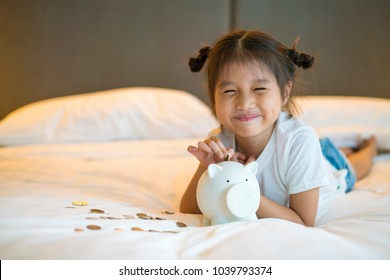 asian cute girl saving money putting coins into piggy bank, vintage tone