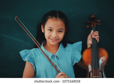 Asian Cute girl with violin on blackboard background