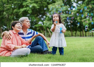 Asian cute granddaughter making bubbles and attractive happy grandparents look at her in the public garden at vacation day or holiday. Family Concept.
