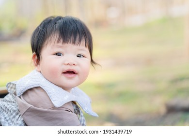 Asian cute happy baby smiling and sitting on a chair. Cute 6 months baby on green bokeh of nature use as mood, health, baby development or kid department in hospital.
