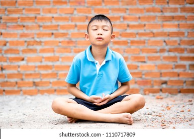 Asian cute kid sitting meditation on ground on brick wall background. Child boy thinking and brain gym. She focusing mind on a head to achieve a mentally clear and emotionally calm state