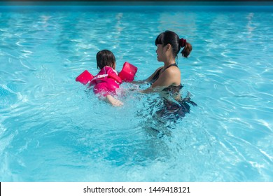 Asian cute little baby girl swimming underwater from mother take care in a pool, child learning to swim lessons and early development concept